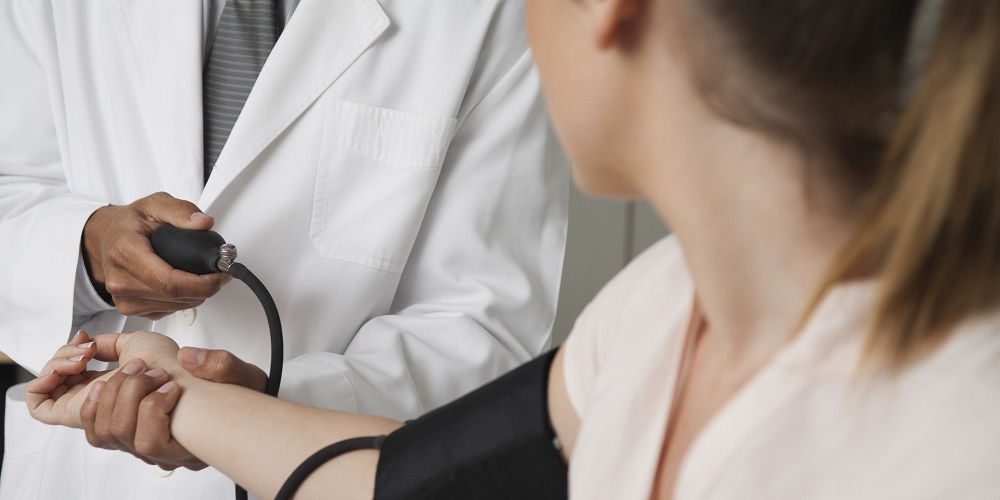 Doctor checking patient's blood pressure, cropped