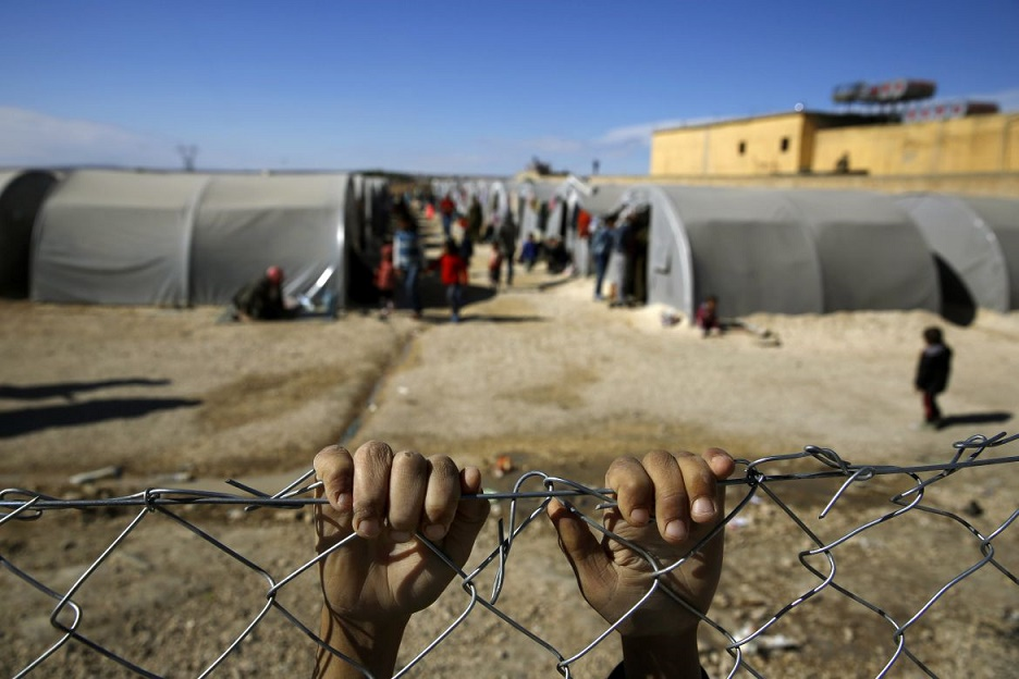 A Kurdish refugee boy from the Syrian town of Kobani holds onto a fence that surrounds a refugee camp in the border town of Suruc, Sanliurfa province November 3, 2014.  REUTERS/Yannis Behrakis (TURKEY - Tags: TPX IMAGES OF THE DAY CONFLICT POLITICS CIVIL UNREST) - RTR4CLQC