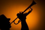 backlight musician playing trumpet on orange background
